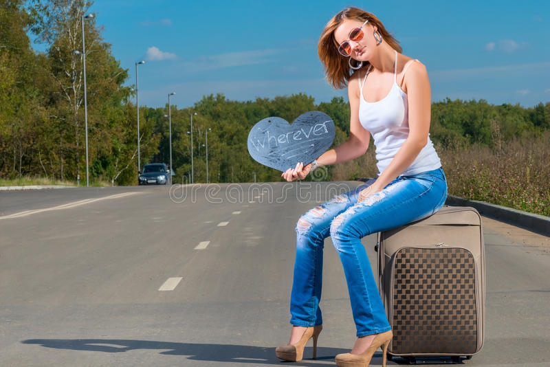 Hitchhiking girl sitting on a suitcase. And waiting for a car stock photography
