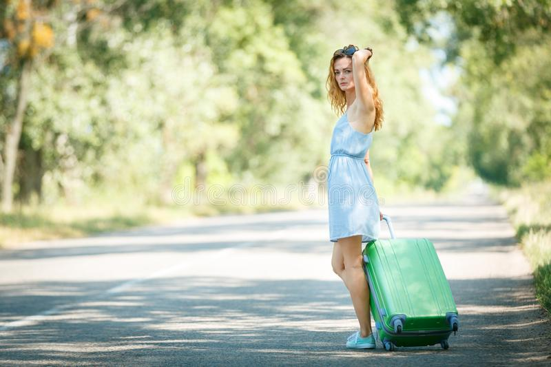 Hitchhiking girl looking for adventures. Hitchhiking girl in a summer dress on a road with a green plastic case. Road adventure concept stock photo