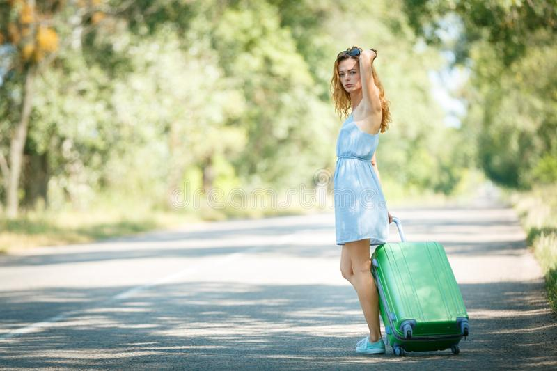 Hitchhiking girl looking for adventures. Hitchhiking girl in a summer dress on a road with a green plastic case. Road adventure concept royalty free stock photography