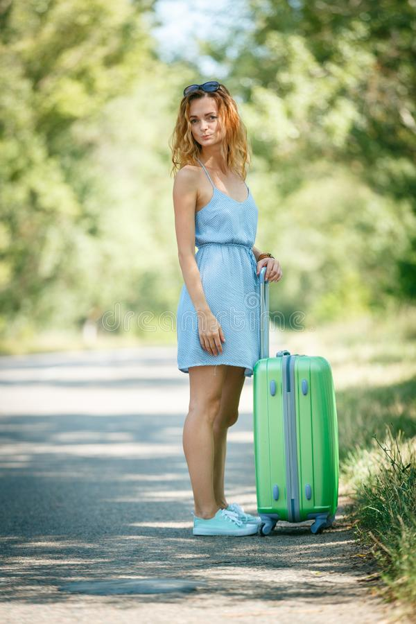 Hitchhiking girl looking for adventures. Hitchhiking girl in a summer dress on a road with a green plastic case. Road adventure concept royalty free stock photos