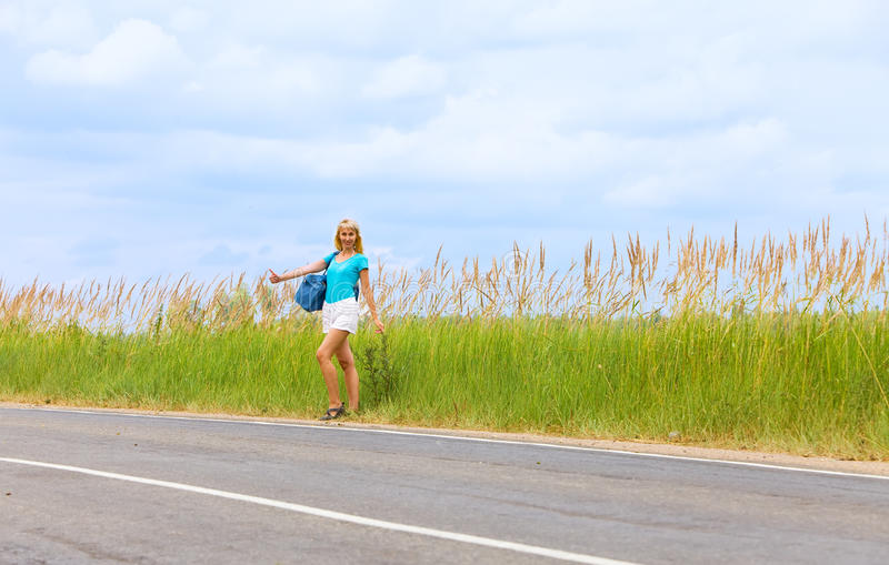 Hitchhiking girl votes on road. Genre scene stock photos
