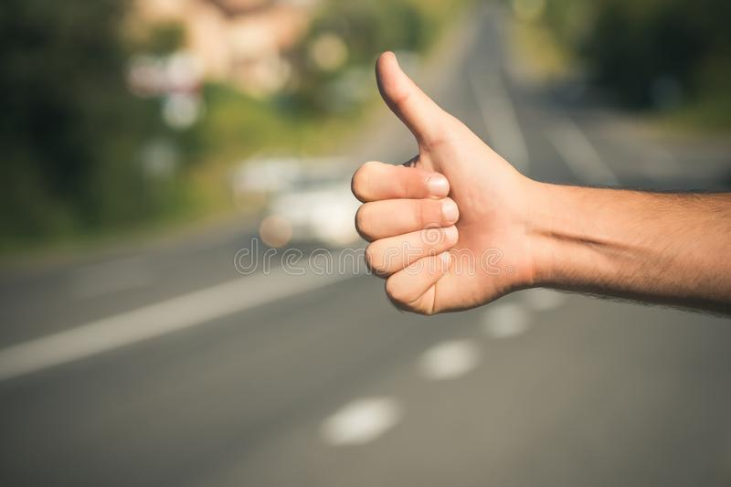 Hitchhiking, hitching, thumbing, auto stop concept. Thumbs up male hand gesture outdoors. Hitchhiker sign on road. Travel, trip, vacation wanderlust royalty free stock images