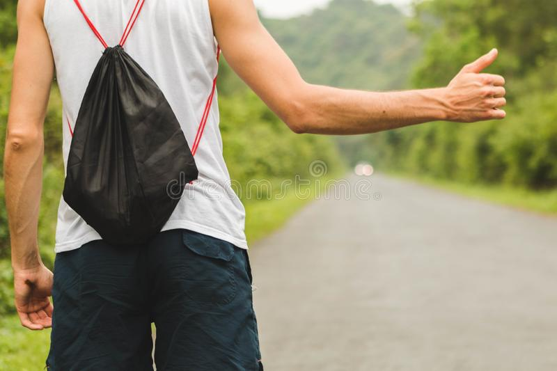 Hitchhiking on mountain road. Lonely man trying to stop a car in the middle of nowhere. Young man hitchhiking on mountain road in Vietnam. Autostop concept royalty free stock images