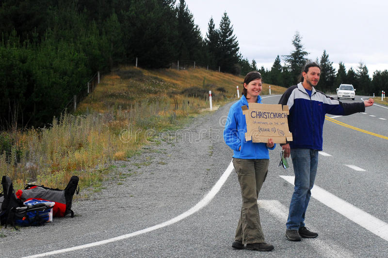 Hitchhiking in New Zealand. LAKE TEKAPO, NZ - MARCH 01: Young couple are Hitchhiking in south island of New Zealand on March 01 2009. New Zealand is one of the royalty free stock images