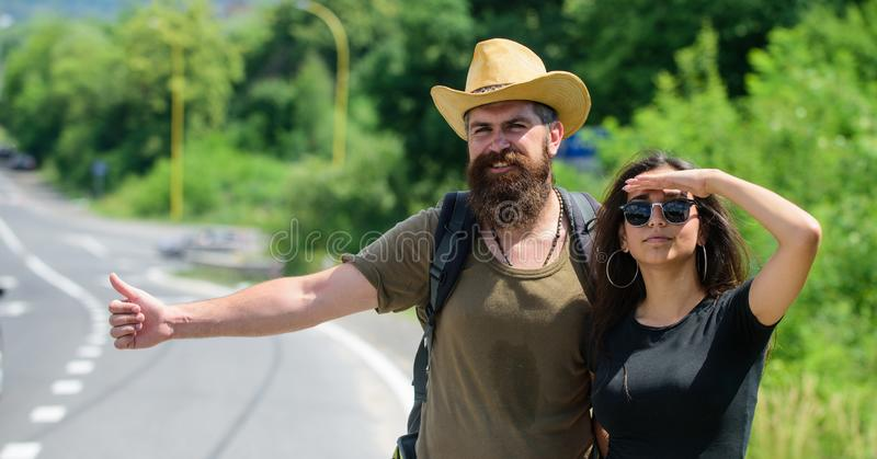 Hitchhiking is one of cheapest ways of traveling. Couple hitchhikers travelling summer sunny day. Couple travelers man stock photo