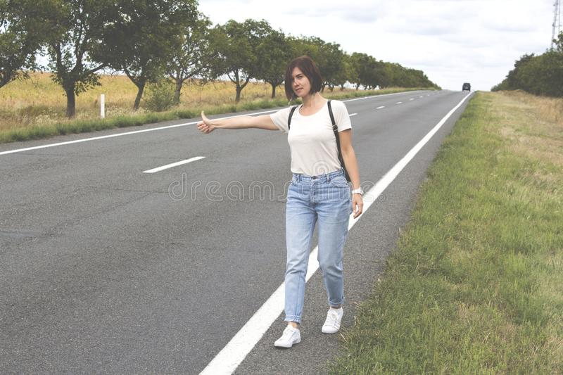 Hitchhiking the road. Female hand gesture, road trip, travel. Young woman with a backpack hitch-hiking on a road at the fields. concept of people royalty free stock photography