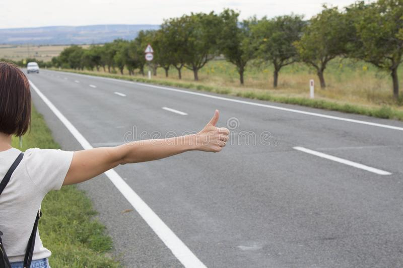 Hitchhiking the road. Female hand gesture, road trip, travel. Young woman with a backpack hitch-hiking on a road at the fields. concept of people stock images