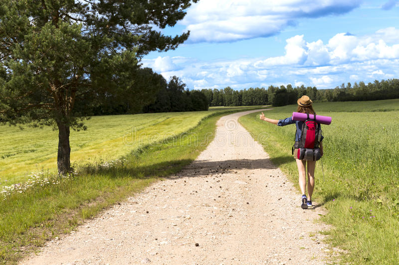 Hitchhiking road travel. Woman with a big backpack trying to stop a ride by thumbing royalty free stock image
