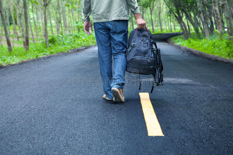 Hitchhiking tourism concept. Travel hitchhiker man with backpack. Walking on the road passes through beautiful forests stock images