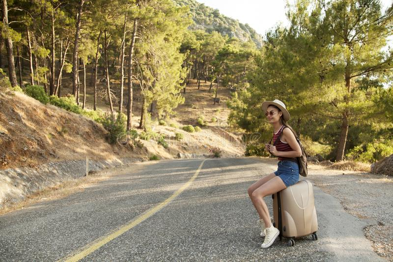 Hitchhiking tourism concept. Travel hitchhiker woman walking on road during holiday travel royalty free stock images