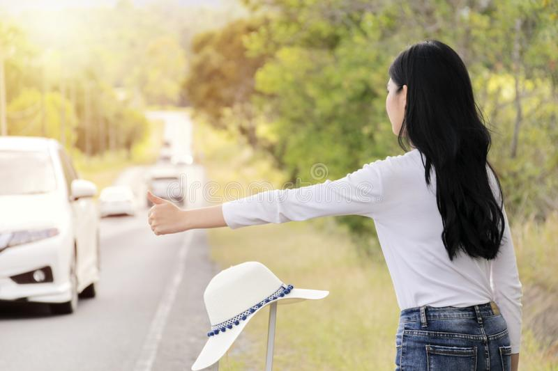 Hitchhiking tourism concept. Traveling alone, When there is a problem, need help. Hitchhiking tourism concept. Travel hitchhiker woman walking on road during royalty free stock photo