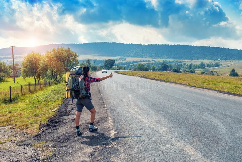 Hitchhiking, tourist with backpack. On the road stock photography