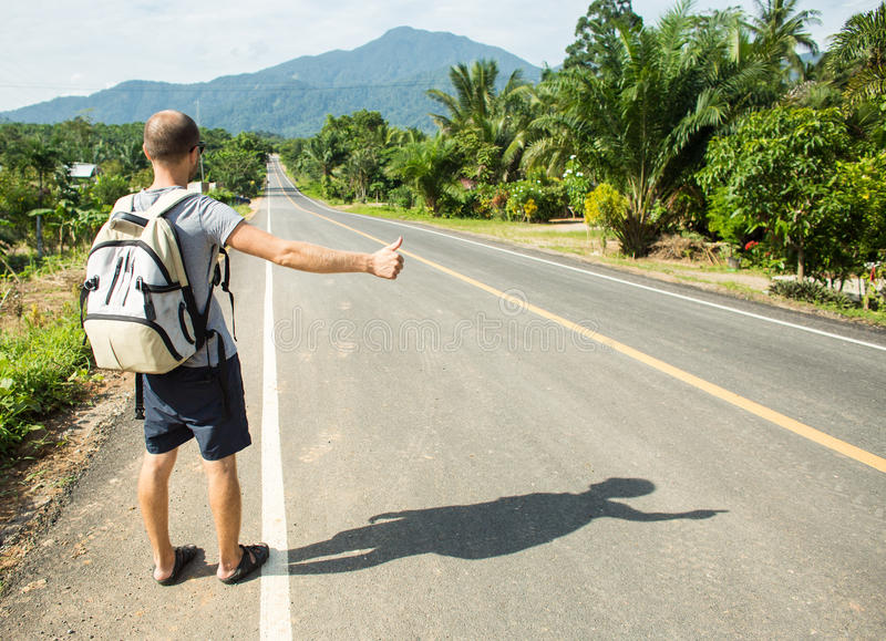 Hitchhiking traveler try to stop car on the mountain road. Hitchhiking traveler try to stop car on mountain road stock image