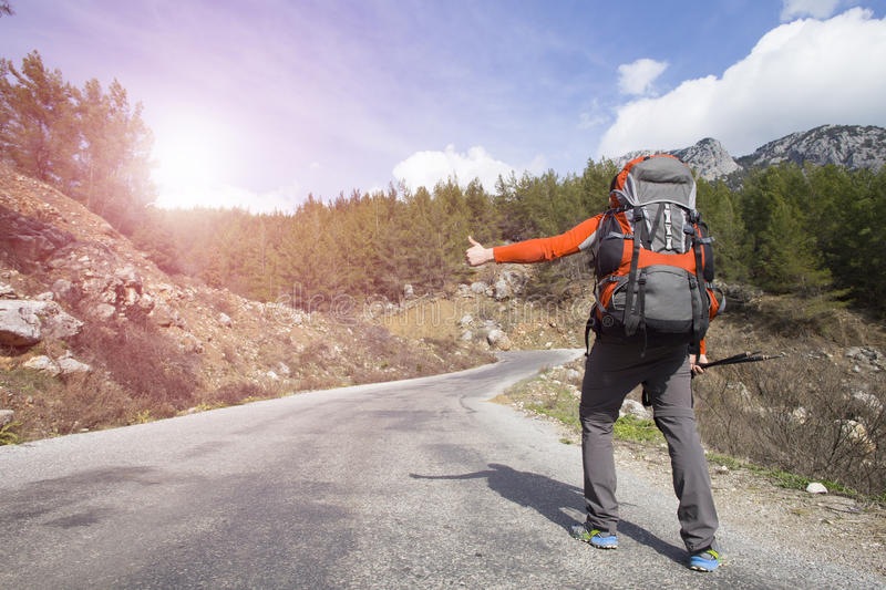 Hitchhiking traveler try to stop car on the mountain road.  royalty free stock photos