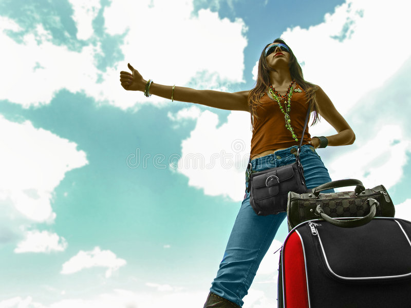 Hitchhiking Woman. Serious young woman with her thumb outstretched hitchhiking, her luggage piled on the ground by her foot. Shot from a low perspective upward royalty free stock photos