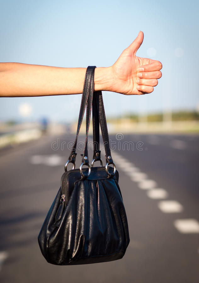 Hitchhiking. Woman hand with black bag, hitchhiking concept royalty free stock photo