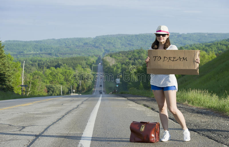 Hitchhiking. Young girl hitchhiking with placards in hand royalty free stock photo