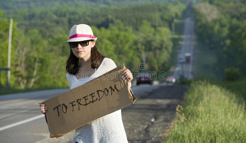 Hitchhiking. Young girl hitchhiking with placards in hand stock image
