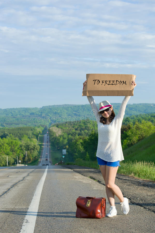 Hitchhiking. Young girl hitchhiking with placards in hand royalty free stock photography