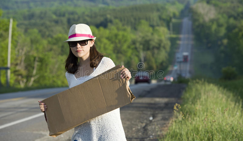 Hitchhiking. Young girl hitchhiking with placards in hand stock photo