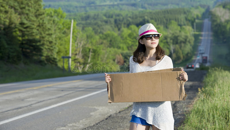 Hitchhiking. Young girl hitchhiking with placards in hand stock images