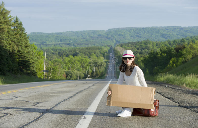 Hitchhiking. Young girl hitchhiking with placards in hand royalty free stock image