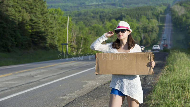 Hitchhiking. Young girl hitchhiking with placards in hand stock photography