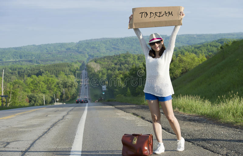 Hitchhiking. Young girl hitchhiking with placards in hand royalty free stock photos