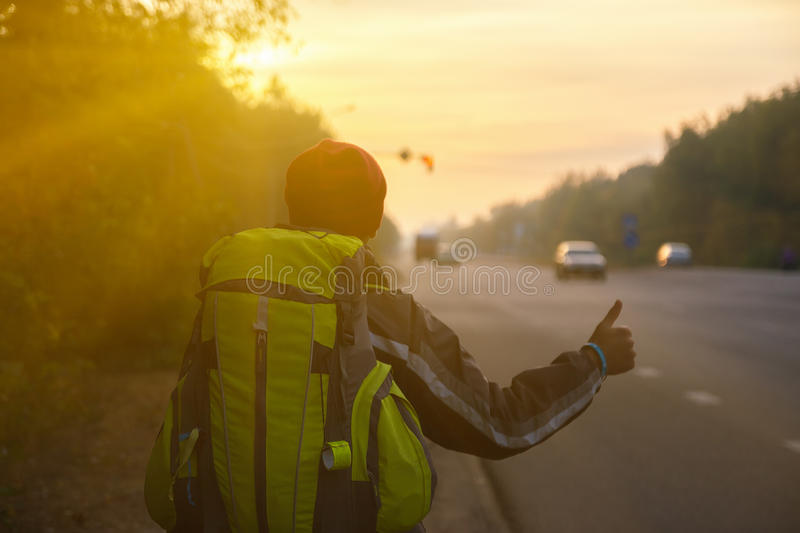 Hitchhiking young traveller trying to catch car. Hitchhiking young traveller try to catch car in the morning stock photos