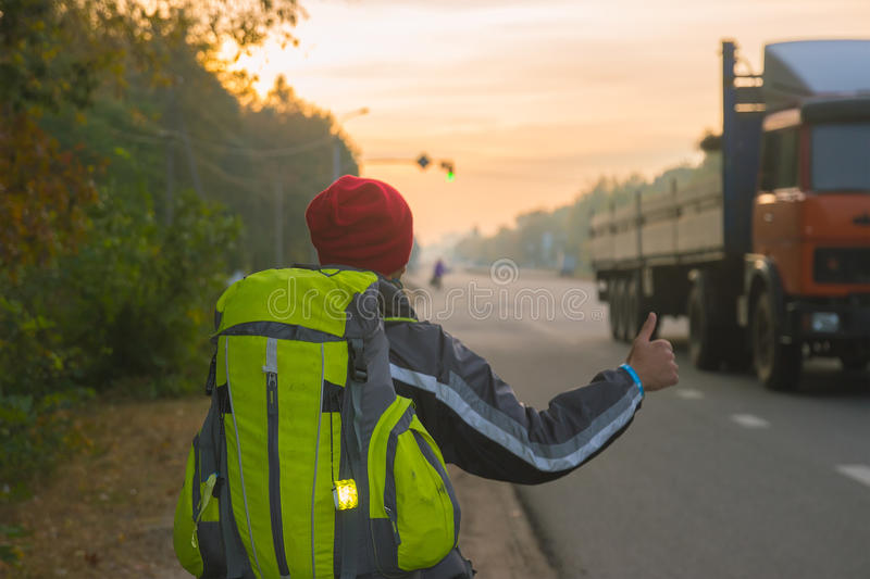Hitchhiking young traveller trying to catch car. Hitchhiking young traveller try to catch car in the morning royalty free stock image