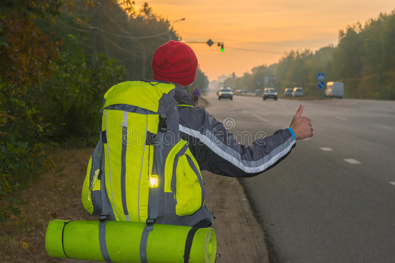 Hitchhiking young traveller trying to catch car. Hitchhiking young traveller try to catch car in the morning with reflector on backpack royalty free stock photo