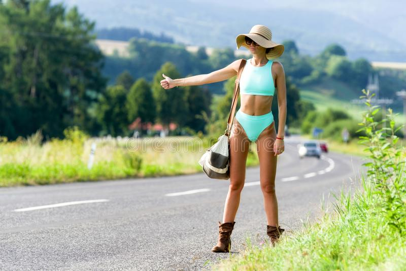 Hitchhiking girl on road royalty free stock image