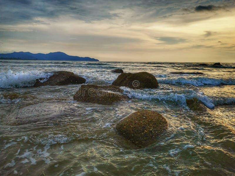 HiThe härligt landskap på den steniga stenen under solnedgångsikten på havskusten och den livliga vattenreflexionen arkivfoton