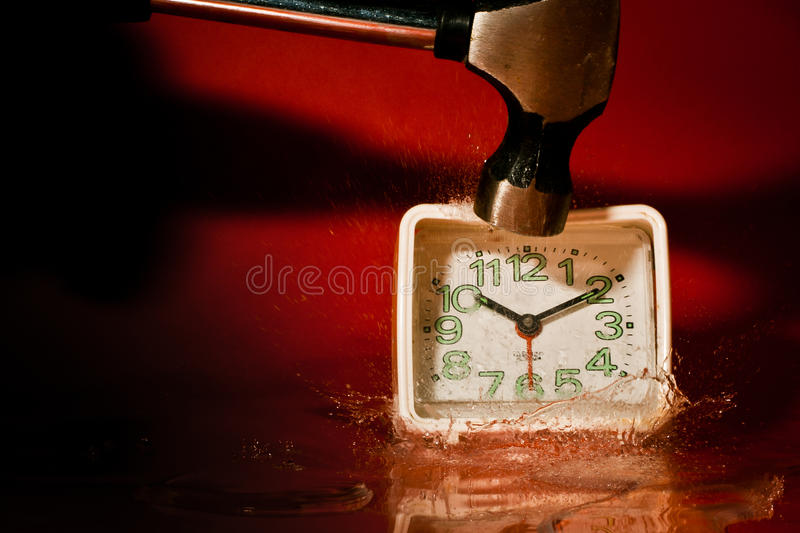 Hitting a clock with a hammer stock photos