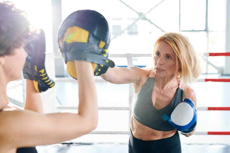 Hitting target. Blonde aggressive sportswoman hitting her young rival with boxing glove while preparing for competition stock photo