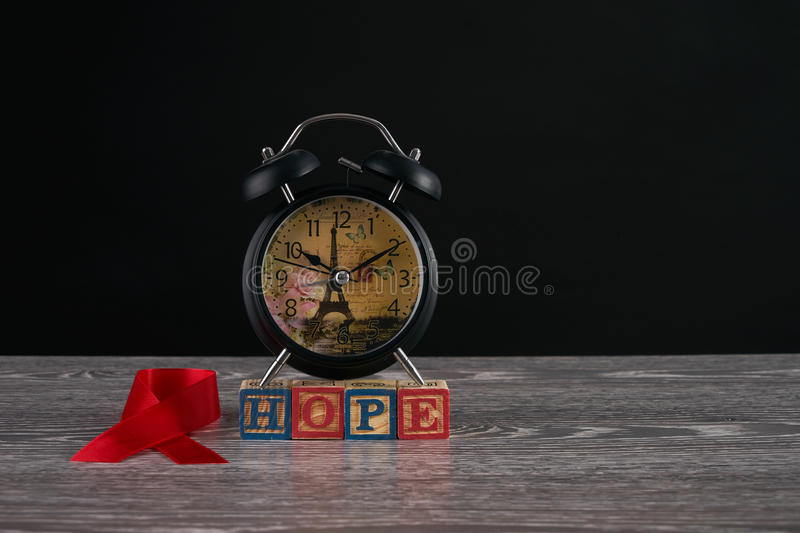 HIV AIDS. Alarm clock, red awareness ribbon and hope word on cubes with letters. Symbol of solidarity with people living with HIV AIDS. Healthcare and medicine stock photo