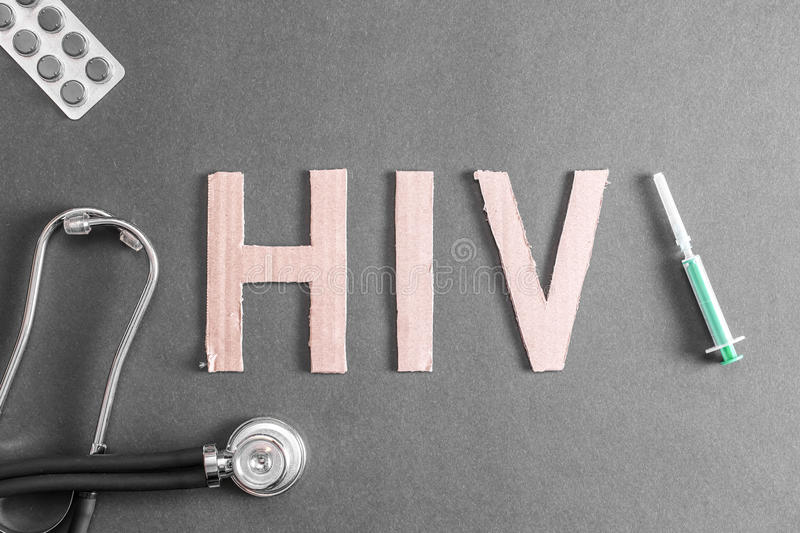 HIV background. A stethoscope, pills and a disposable syringe on a dark background together with the word HIV made out of cardboard for your concepts royalty free stock images