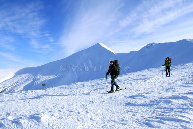 Hiver augmentant dans les montagnes avec un sac à dos et une tente photo stock