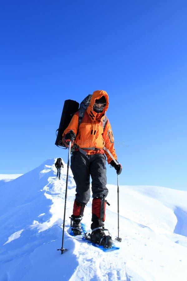 Hiver augmentant dans les montagnes sur des raquettes avec un sac à dos et une tente photographie stock