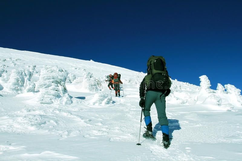 Hiver augmentant dans les montagnes sur des raquettes avec un sac à dos et une tente image libre de droits