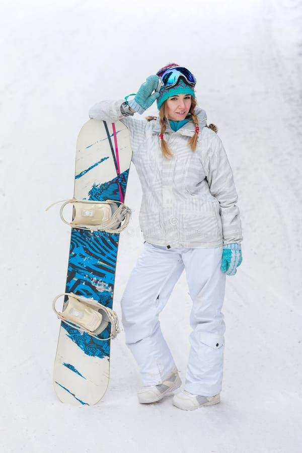 Hiver, concept de sport, jeune femme heureuse avec le surf des neiges dehors images stock