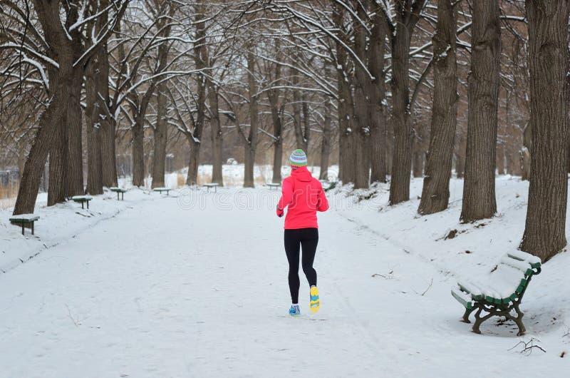 Hiver fonctionnant en parc : coureur heureux de femme pulsant dans la neige, le sport en plein air et la forme physique photos libres de droits
