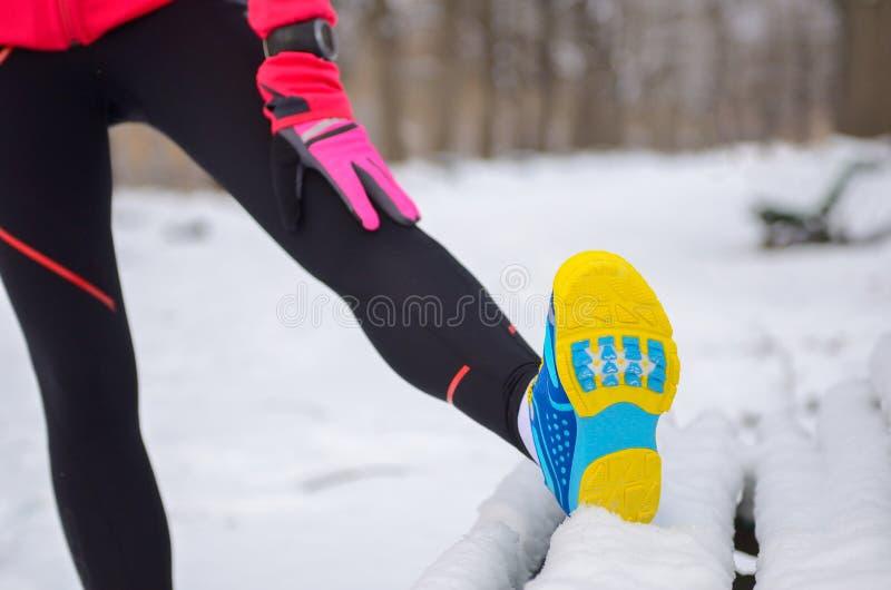 Hiver fonctionnant en parc : plan rapproché de vêtements de sport dans la neige, femme s'étirant avant essai, forme physique exté images libres de droits
