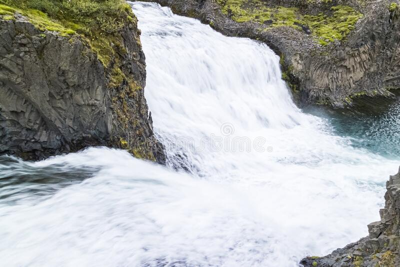 Helper waterfall Hjálparfoss in a Fossá in Iceland. Hjelpfoss is a double waterfall at the bottom of Fossá in Þjórsárdalur, just before it merges stock photo