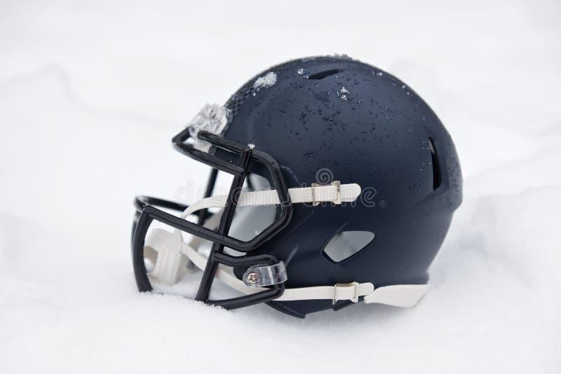 Hjälm för amerikansk fotboll i snö arkivbild
