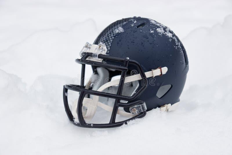 Hjälm för amerikansk fotboll i snö arkivfoto