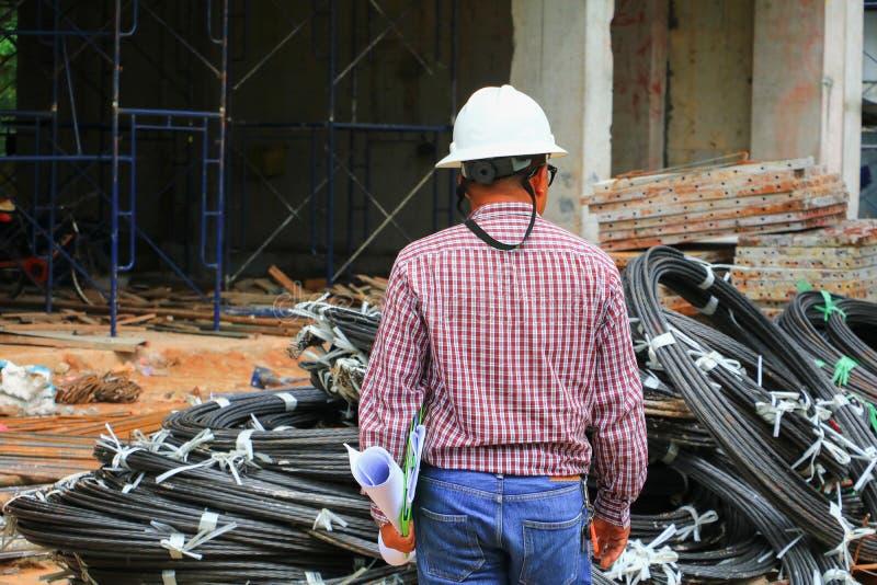 hjälm för Arkitekt-tekniker affärsmankläder i konstruktionsbyggnadsplatsen, baksidasikt fotografering för bildbyråer