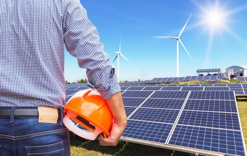 Hjälm för guling för säkerhet för teknikerställning hållande med sol- celler och vindturbiner som frambringar elektricitet i hybr arkivfoto