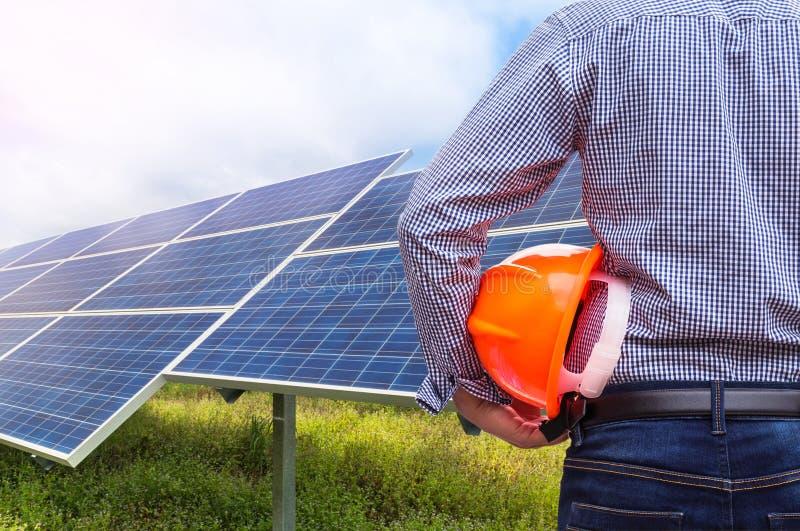 Hjälm för konstruktion för guling för teknikerställningsinnehav i solenergistation royaltyfri bild