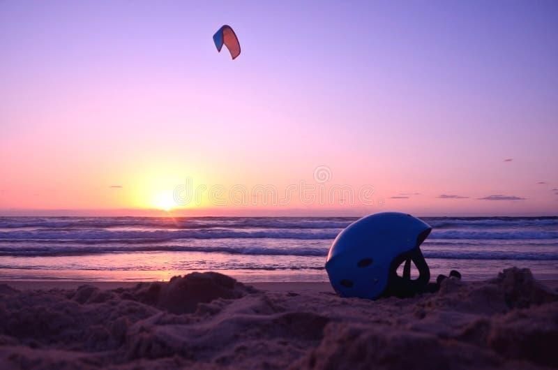 Hjälm- och drakesurfare i havet solnedgång strand av medelhavet Säkerhet jämvikt, extrema sportar arkivfoto